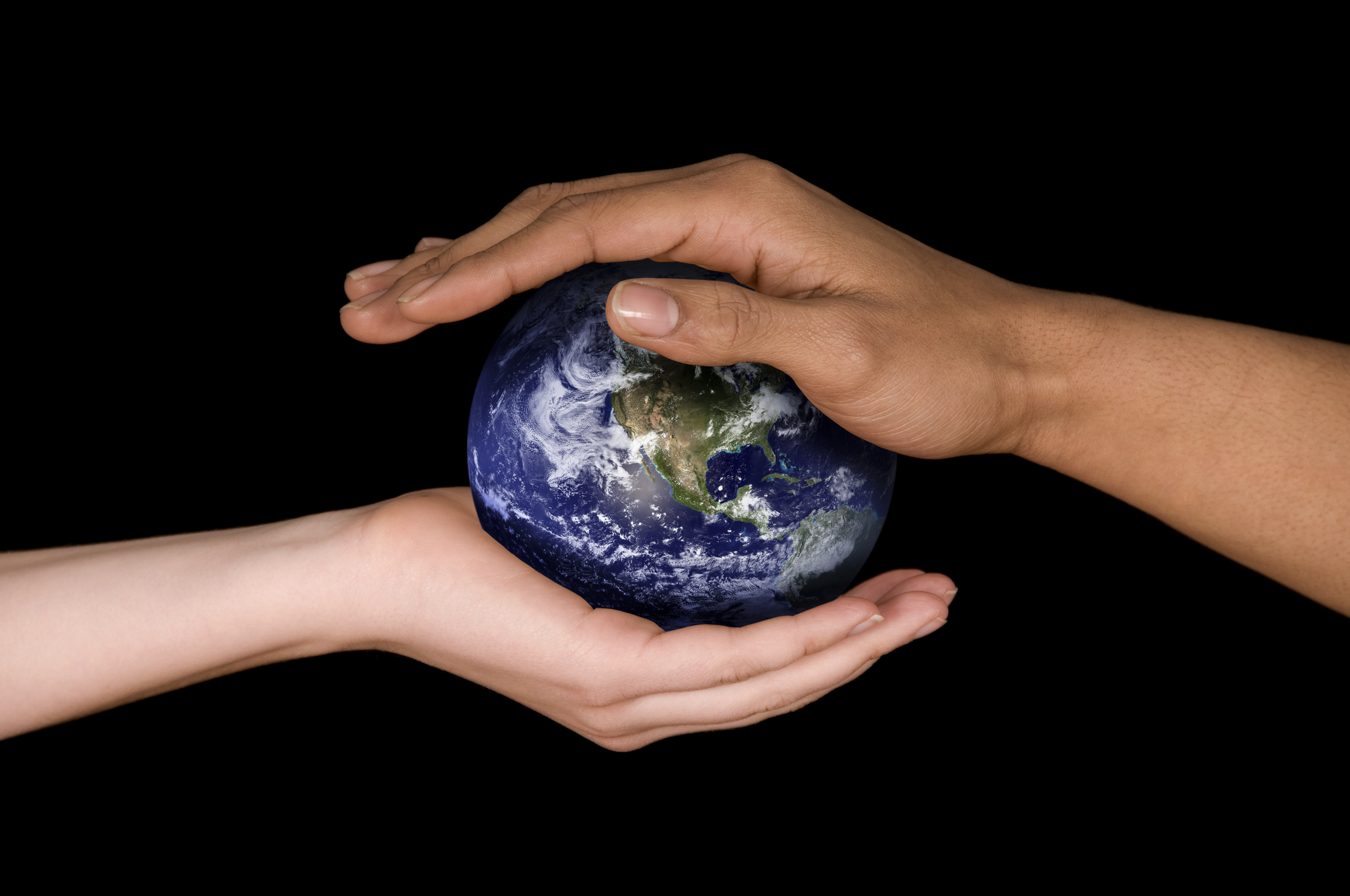 two hands holding a planet earth on black